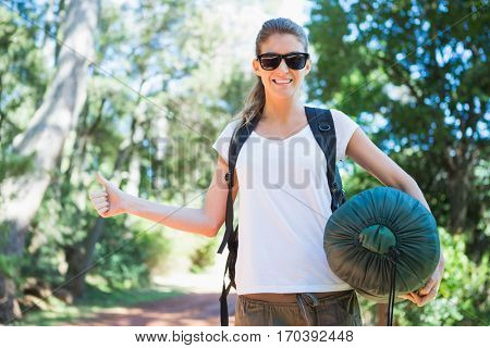 Hitch hiking woman with sleeping bag in the countryside