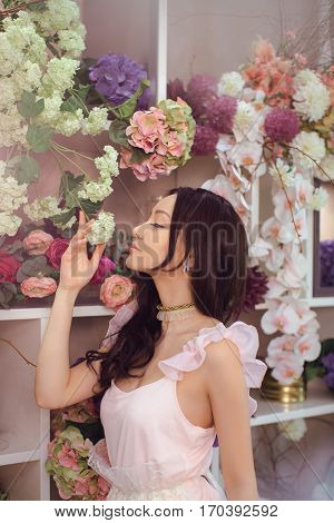 Beautiful girl in tender pink dress standing against floral background in flower shop. Joyful asian female florist. Playful fashion model smells spring flowers.