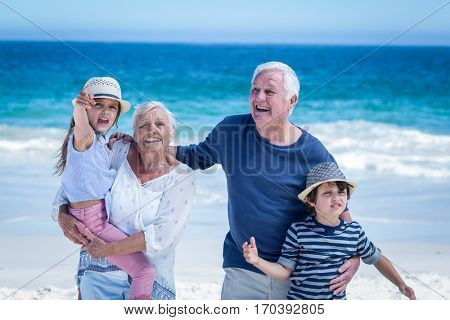 Happy grandparents giving piggy back to children on the beach