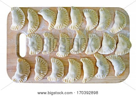 Dumplings with cherry filling closeup in the flour on the cutting board isolated over white