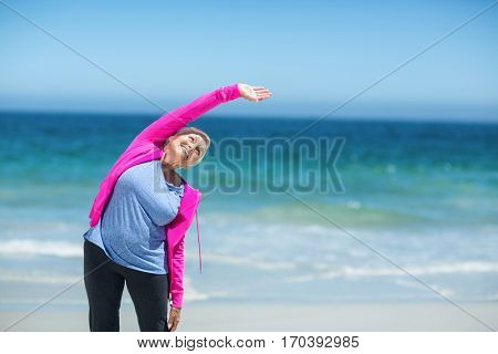 Mature woman outstretching her arms on the beach