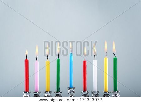 Menorah with colorful candles for Hanukkah on light background, close up