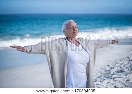 Beautiful mature woman outstretching arms at the beach