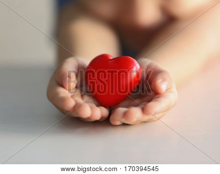 Child holding small red heart, closeup. Adoption concept