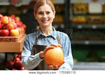 Beautiful saleswoman with fruits in market