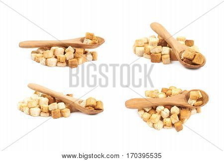 Pile of garlic white bread croutons with a wooden spoon over it, composition isolated on the white background, set of four different foreshortenings