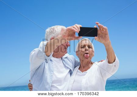 Senior couple taking a selfie and grimacing at the beach
