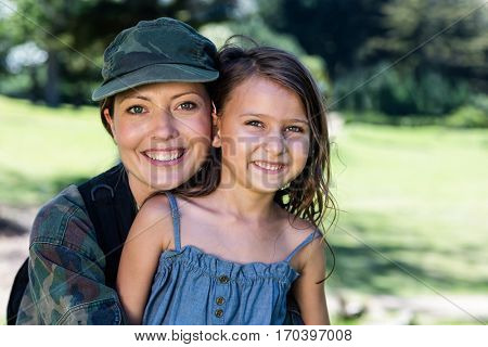 Portrait of happy soldier reunited with her daughter in the park on a sunny day