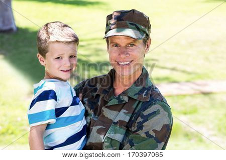 Portrait of happy soldier reunited with his son in the park on a sunny day