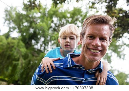 Portrait of father giving a piggy back to his son in the park