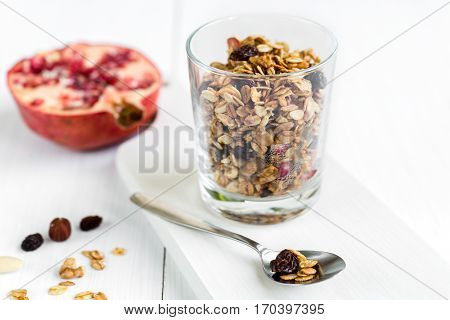 Fresh granola muesli in a glass with almonds raisins and pomegranate. Healthy breakfast.