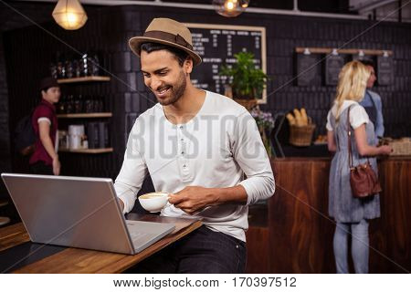 Man using a laptop and drinking coffee in a coffee shop