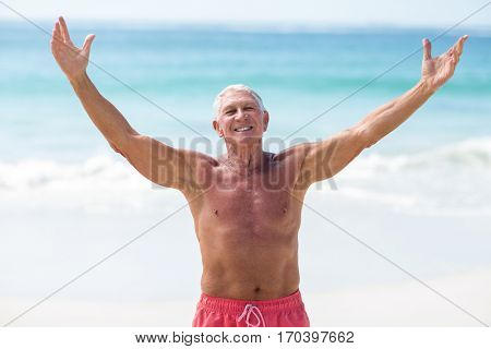 Handsome mature man outstretching his arms on the beach