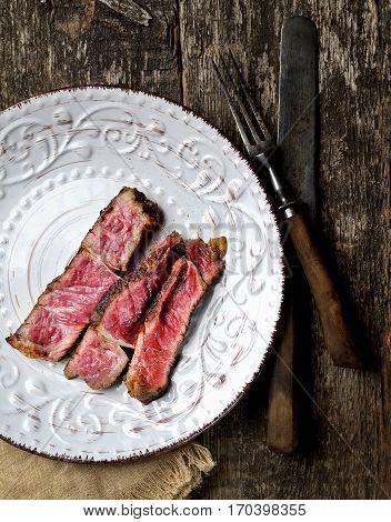 Sliced medium rare grilled Beef steak Ribeye on a plate