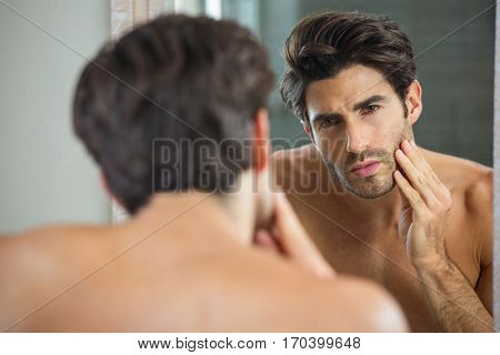 Reflection of young man checking his stubble in bathroom mirror