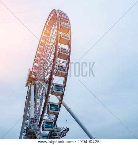 Big ferris wheel with cloudy sky .