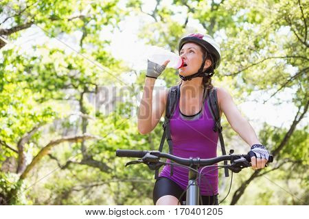 Woman drinking water while cycling in the countryside