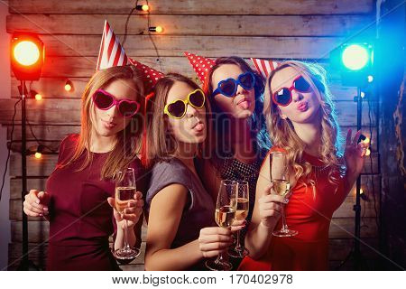 Birthday party girlfriends. Beautiful girls in caps, and colored glasses with champagne glasses grimace shows language.