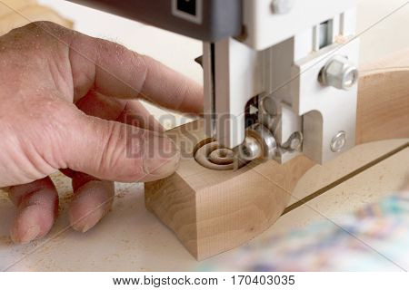 Carpenter tools on wooden table with sawdust. Band-saw to cut an intricate shape in a piece of wood.Carpenter workplace.