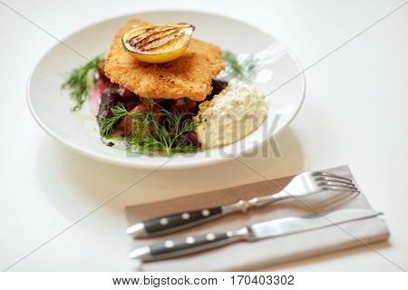 food, new nordic cuisine, dinner, culinary, haute cuisine and cooking concept - close up of breaded fish fillet with tartar sauce and oven-baked beetroot tomato salad on plate