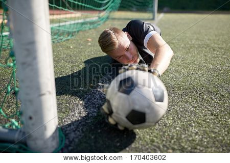 sport and people - soccer player or goalkeeper lying with ball at football goal on field