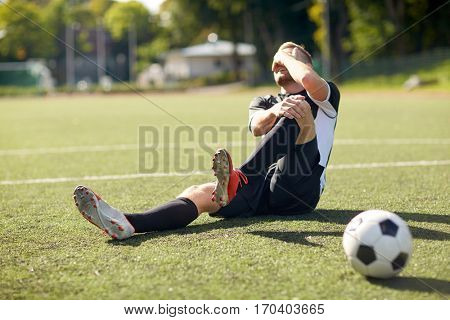 sport, football training, sports injury and people - injured soccer player with ball on field