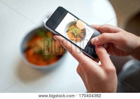 food, new nordic cuisine, technology, eating and people concept - woman with smartphone photographing bowl of seafood soup with fish and blue mussels at restaurant