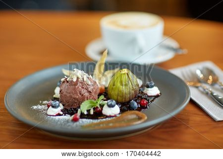food, new nordic cuisine and sweets concept - chocolate ice cream dessert with blueberry kissel, honey baked fig and greek yoghurt on plate at restaurant