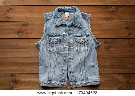 clothes, wear and fashion concept - denim vest or waistcoat on wooden background