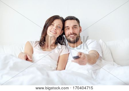 people, rest, love, relationships and television concept - happy couple with remote lying in bed at home and watching tv