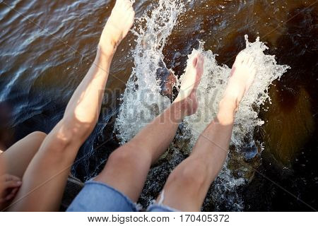 holidays, vacation, love and people concept - legs of couple sitting on berth and splashing water in river or lake at summer