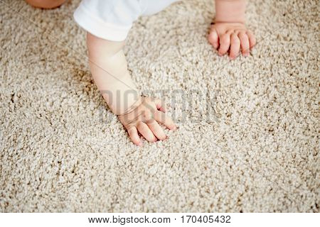 childhood, babyhood and people concept - hands of baby crawling on floor or carpet