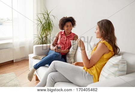 friendship, leisure, people and communication concept - happy women with drink sitting on sofa and talking gat home