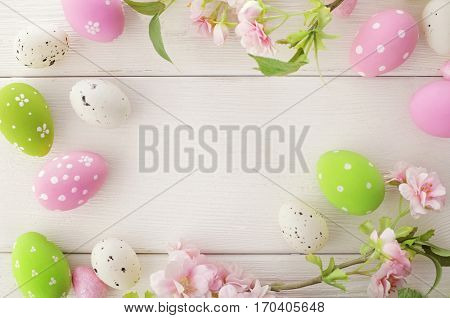 frame background with colorful easter eggs and spring flowers