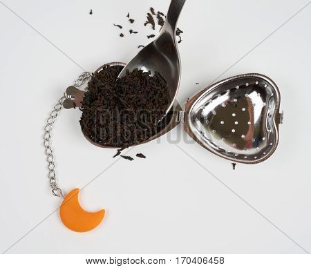 Putting a spoon of black tea in the tea strainer