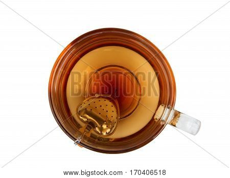 Cup of tea and tea strainer with heart shape. Upper view.