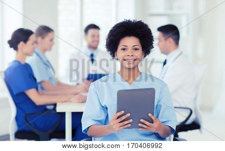 clinic, profession, people and medicine concept - happy female doctor or nurse with tablet pc computer over group of medics meeting at hospital