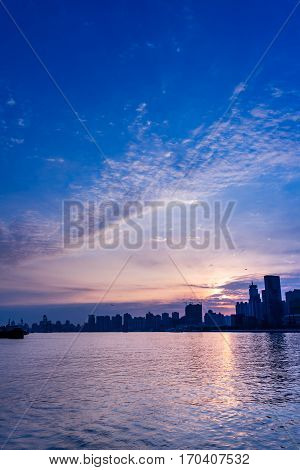 City Skyline By River Against cloudy Sky in Shanghai China.