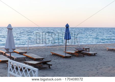 Seascape with sunbeds, sunshades in summer in afternoon