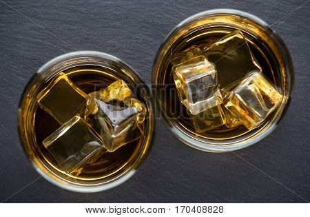 Two round glasses aged whiskey with ice on slate blackboard