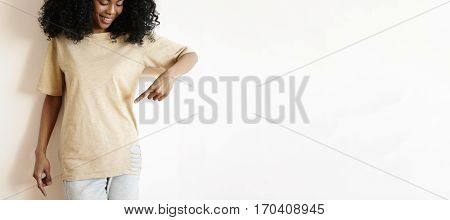 Happy Young African Model With Afro Hairstyle Posing At White Copy Space Studio Wall, Pointing Her I