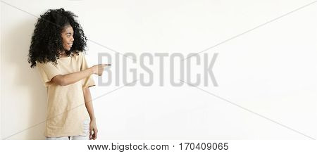 Attractive Young African Female With Afro Hairstyle Posing Indoors At White Studio Wall, Looking Awa