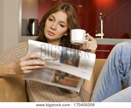 Portrait of a young adult beautiful attractive pretty brunette woman drinking coffee and reading newspaper