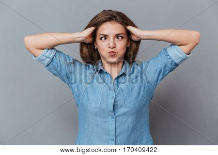 Funny Woman in shirt holding her hair and showing grimace in studio. Isolated gray background