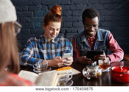 People, Communication And Modern Technology. Internet Addicted Interracial Couple Holding Their Gadg