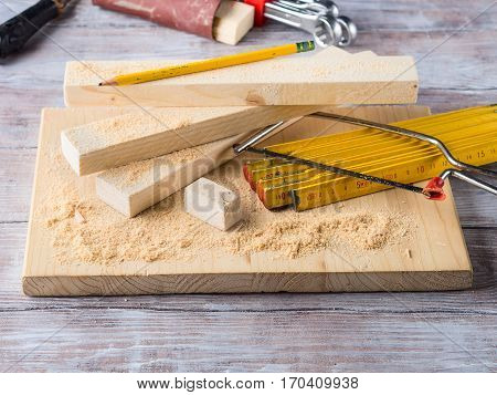 Wooden board with tools for manual measuring cutting - meter, level, pencil. Bricolage hand made DIY design craft project.