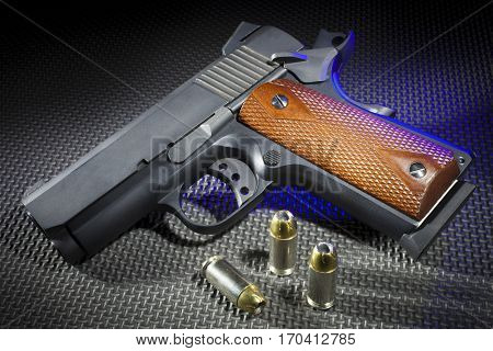 Handgun on a rubber mat with ammo and a blue rim light