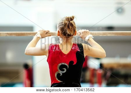 prepare girl athlete gymnast exercises on parallel bars