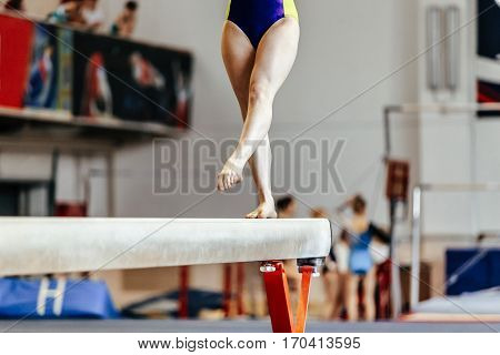 young girl athlete gymnast on balance beam competition in gymnastics