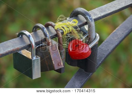 Red heart-shaped lock are hanging on the bridge lovers